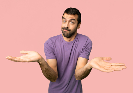 Handsome man having doubts while raising hands and shoulders on isolated pink background