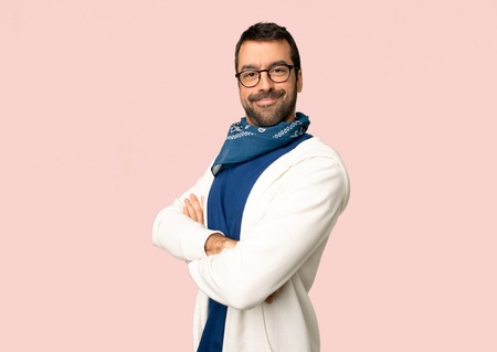 Handsome man with glasses keeping the arms crossed in lateral position while smiling on isolated pink background