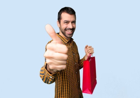 Man with shopping bags giving a thumbs up gesture because something good has happened on isolated blue background Imagens