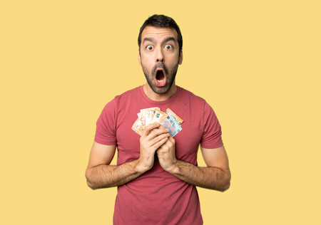 Man taking a lot of money with surprise and shocked facial expression on isolated yellow background Stok Fotoğraf