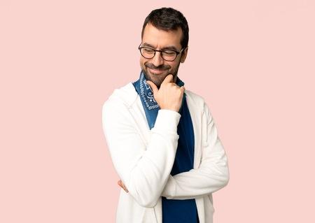 Hombre guapo con gafas mirando hacia abajo con la mano en la barbilla sobre fondo rosa aislado