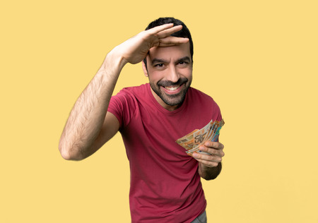 Man taking a lot of money looking far away with hand to look something on isolated yellow background 写真素材