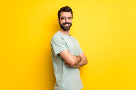 Man with beard and green shirt keeping the arms crossed in lateral position while smiling Stok Fotoğraf