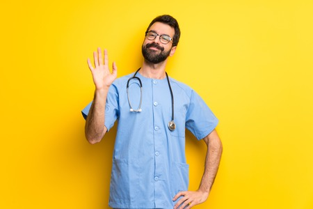 Surgeon doctor man saluting with hand with happy expression