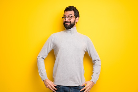 Man with beard and turtleneck posing with arms at hip and laughing looking to the front