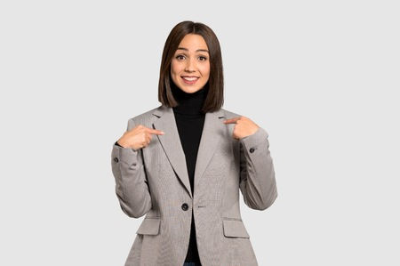 Young business woman with surprise facial expression on isolated grey background