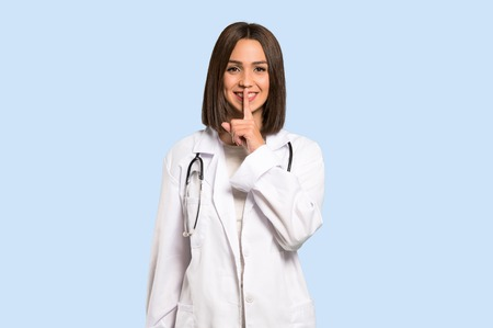 Young doctor woman showing a sign of silence gesture on isolated blue background