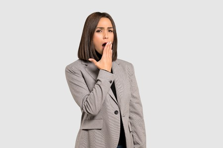 Young business woman yawning and covering wide open mouth with hand on isolated grey background Imagens