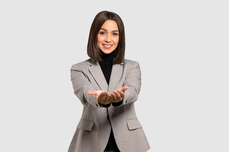 Young business woman holding copyspace imaginary on the palm to insert an ad on isolated grey background