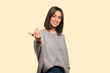Mujer joven que invita a venir con la mano. Feliz de que hayas venido sobre fondo amarillo aislado