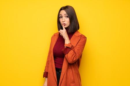Jonge vrouw met jas die een teken van stilte toont die vinger in mond steekt