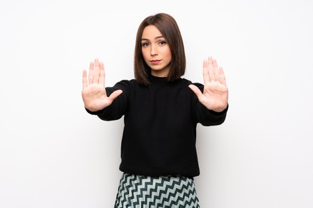 Young woman over white wall making stop gesture and disappointed
