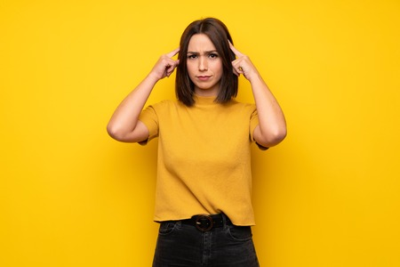 Young woman over yellow wall having doubts and thinking