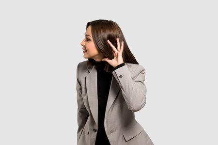 Young business woman listening to something by putting hand on the ear on isolated grey background Imagens
