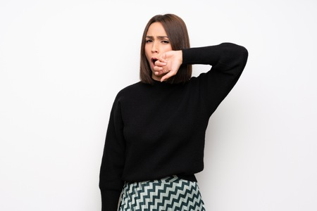 Young woman over white wall yawning and covering wide open mouth with hand Stock Photo