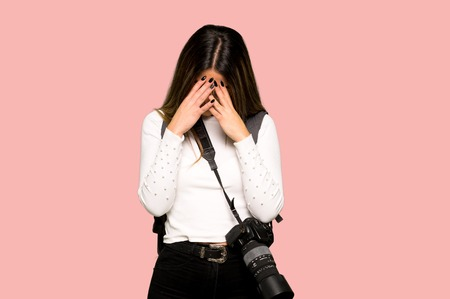Young photographer woman with tired and sick expression on isolated pink background