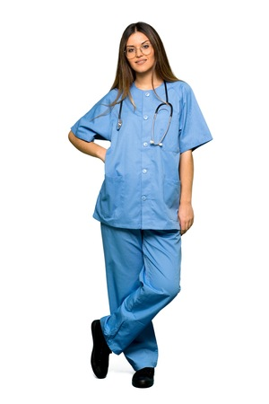 Full body of Young nurse posing with arms at hip and smiling