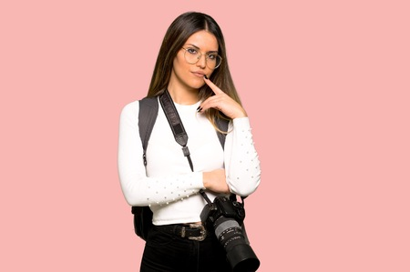 Young photographer woman having doubts while looking up on isolated pink background