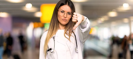 Young doctor woman showing thumb down sign with negative expression in a hospital