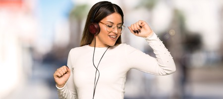 Pretty woman with glasses listening to music with headphones and dancing at outdoors Imagens