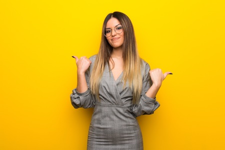 Young woman with glasses over yellow wall giving a thumbs up gesture with both hands and smiling 版權商用圖片