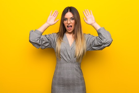 Young woman with glasses over yellow wall with surprise and shocked facial expression