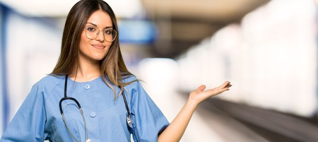 Young nurse holding copyspace imaginary on the palm to insert an ad in a hospital