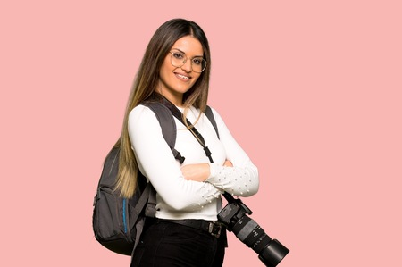 Young photographer woman with arms crossed and looking forward on isolated pink background Imagens