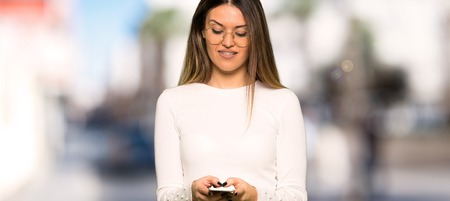 Pretty woman with glasses using mobile phone at outdoors Imagens