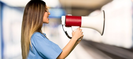 Young nurse shouting through a megaphone in a hospital