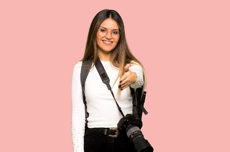 Young photographer woman shaking hands for closing a good deal on isolated pink background
