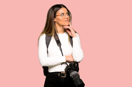 Young photographer woman thinking an idea while looking up on isolated pink background