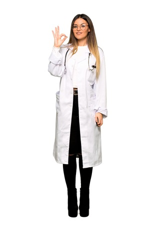 Full body of Young doctor woman showing an ok sign with fingers