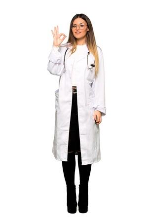 Todo el cuerpo de la mujer joven médico que muestra un signo de ok con los dedos
