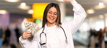 Young doctor woman taking a lot of money in a hospital
