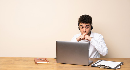 Telemarketer man showing a sign of silence gesture