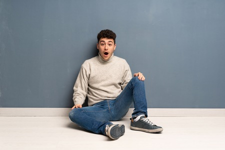 Young man sitting on the floor with surprise facial expression Stok Fotoğraf