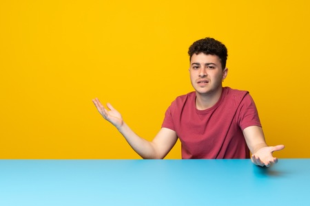 Young man with colorful wall and table unhappy for not understand something