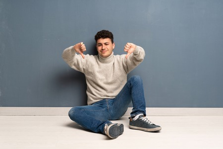 Young man sitting on the floor showing thumb down Banco de Imagens