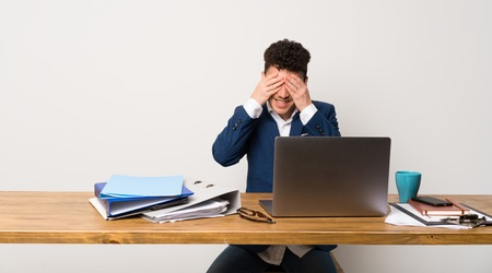 Business man in a office covering eyes by hands