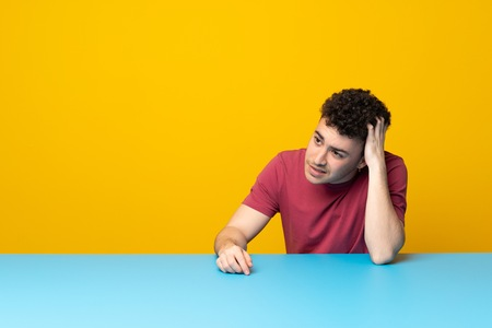 Young man with colorful wall and table thinking an idea Foto de archivo