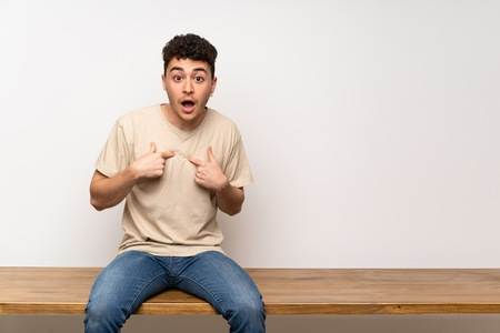 Young man sitting on table with surprise facial expression
