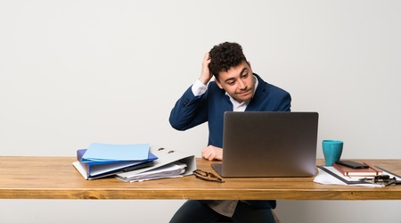 Business man in a office having doubts while scratching head 版權商用圖片