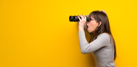 Woman with glasses over yellow wall and looking in the distance with binoculars Stok Fotoğraf
