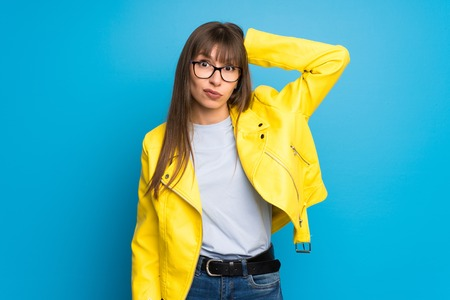 Young woman with yellow jacket on blue background with surprise and shocked facial expression Stok Fotoğraf