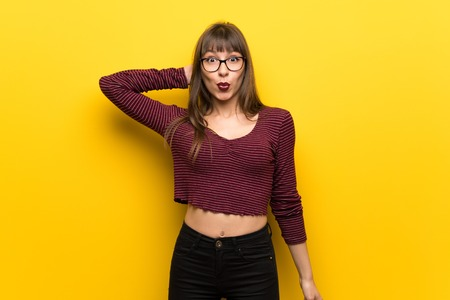 Woman with glasses over yellow wall with surprise facial expression Stok Fotoğraf