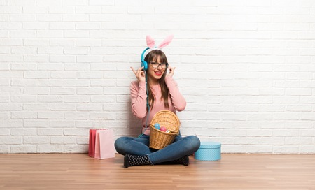 Woman with bunny ears for Easter holidays sitting on the floor listening to music with headphones Stock Photo