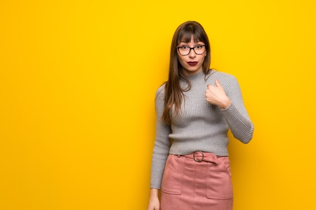 Woman with glasses over yellow wall with surprise facial expression Фото со стока