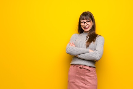 Woman with glasses over yellow wall keeping the arms crossed in frontal position