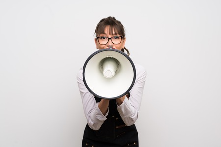 Young woman with apron shouting through a megaphone Imagens